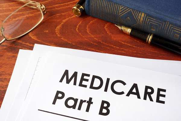 Document labeled 'Medicare Part B' on a desk with glasses and pen