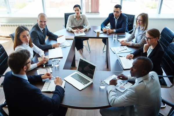 Businespeople conducting negotiations at a conference table in an office setting