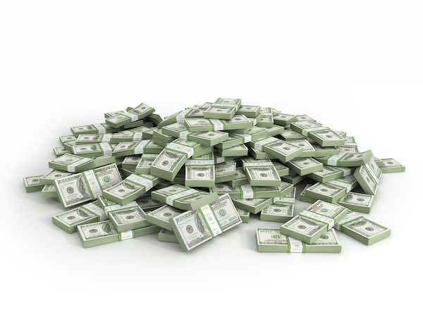 Packs of hundred dollar bills scattered into a large pile against a white background