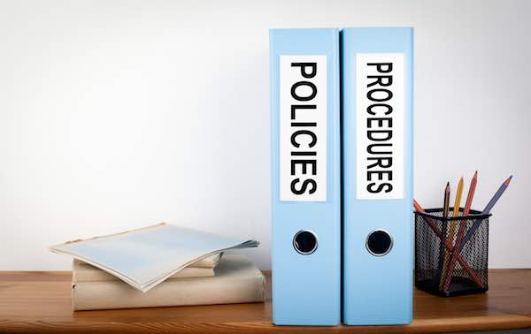 Policies and Procedures binders on a wooden shelf in an office