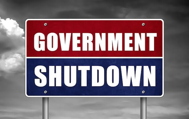 Sign that reads 'government shutdown' pictured against a cloudy grey background