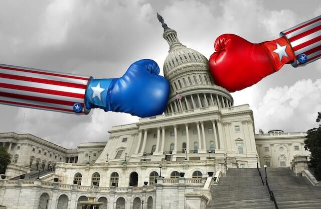 Two boxing gloves coming from both sides, one blue and one red, hitting the Capitol building in Washington, DC depicting a government shutdown fight in Congress