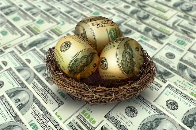Golden eggs with Benjamin Franklin's faces imposed on them to look like $100 bills sitting in a nest on top of a spread of $100 bills depicting a retirement savings nest egg for the future