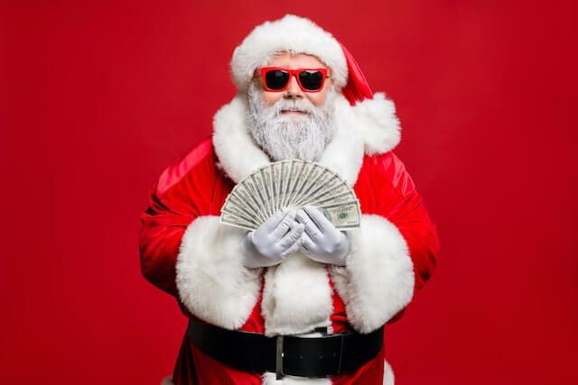 Santa Claus wearing beach sunglasses and holding a fan spread of cash in his hands against a solid red background
