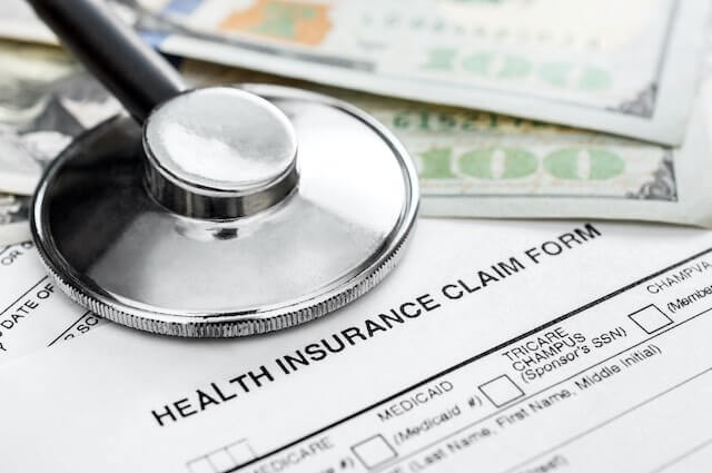 Close up of the top of a document labeled 'health insurance claim form' with a stethoscope and some cash lying on top of it