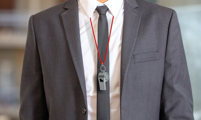 Businessman in a suit wearing a whistle around his neck - whistleblower