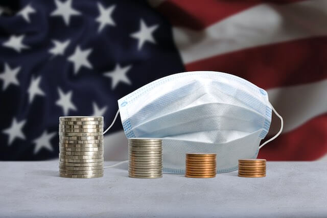 4 vertical stacks of coins decreasing in size from left to right pictured in front of a surgical face mask with a USA flag in the background