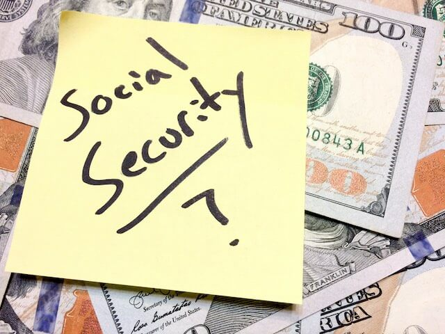 Spread of cash with a yellow post it note on top that reads 'Social Security?'