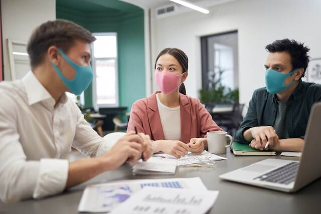 A group of three employees wearing face masks sitting around a table in an office having a meeting